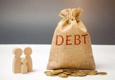 Een zak geld met de woordschuld en de familie die zich dichtbij het huis bevinden Het concept schuld voor huisvesting hypotheek O royalty-vrije stock afbeeldingen