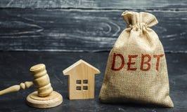 Een zak geld met de woordschuld en de familie die zich dichtbij het huis en de hamer bevinden Het concept schuld voor huisvesting royalty-vrije stock afbeelding