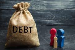 Een zak geld met de woordschuld en de familie Het concept schuld voor bezit hypotheek Onroerende goederen, huisbesparingen, lenin royalty-vrije stock foto