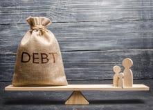 Een zak met de van de inschrijvingsschuld en familie cijfers aangaande de schalen Het concept lounlast op families schuldkuil en  stock foto