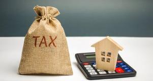 Een zak met de woordbelasting en calculator met een huis Belastingen op onroerende goederen, betaling Sanctie, schuldvorderingen  stock afbeeldingen
