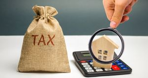 Een zak met de woordbelasting en calculator met een huis Belastingen op onroerende goederen, betaling Sanctie, schuldvorderingen  royalty-vrije stock foto's