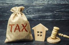 Een zak met geld en de woordbelasting naast een blokhuis Belastingen op onroerende goederen, betaling Sanctie, schuldvorderingen  royalty-vrije stock afbeelding