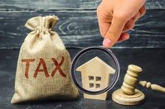 Een zak met geld en de woordbelasting naast een blokhuis Belastingen op onroerende goederen, betaling Sanctie, schuldvorderingen  stock foto