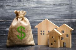 Een zak met geld en drie huizen Concept onroerende goederenaanwinst en investering Betaalbare goedkope lening, hypotheek belastin royalty-vrije stock afbeeldingen