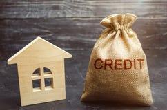 Een zak met geld en het woordkrediet dichtbij het huis Het kopen van een bezit in schuld Lening voor huisvesting Hypotheeklening  stock fotografie