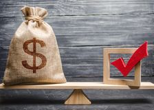 Een zak met geld en een rood vinkje van een stem op schalen Het concept de diensten lobbyt voor wetten en verordeningen vóór stock fotografie