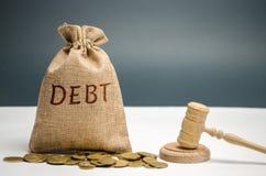Een zak van geld en de woordschuld en de hamer van de rechter Betaling van belastingen en van schuld aan de staat Concept financi stock fotografie