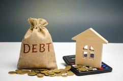 Een zak van geld met de woordschuld en calculator dichtbij het huis Het concept schuld voor huisvesting hypotheek Onroerende goed royalty-vrije stock foto