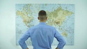 Een zakenman bekijkt een kaart van de wereld stock videobeelden
