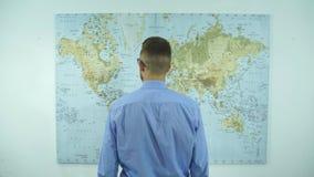 Een zakenman bekijkt een kaart van de wereld stock footage