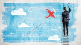 Een zakenman bevindt zich op een trapladder en trekt met een verfrol een blauwe hemel voor een beeldverhaal rood vliegtuig binnen stock fotografie