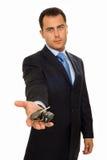 Een zakenman die een bos van autosleutels en auto aanbiedt Stock Afbeeldingen