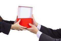 Een zakenman die een giftdoos geven aan zijn die vrouw op wit wordt geïsoleerd Stock Afbeelding
