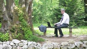 Een zakenman die en een sigaret ontspannen roken stock videobeelden
