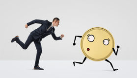 Een zakenman die na een gouden muntstuk met armen en benen op witte achtergrond lopen Royalty-vrije Stock Foto