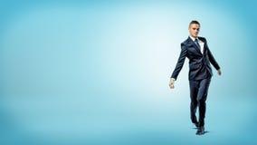 Een zakenman die op blauwe achtergrond op onvaste benen zoals een gebroken pop lopen stock fotografie