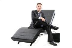 Een zakenman die op een bank wordt gesitueerd stock fotografie