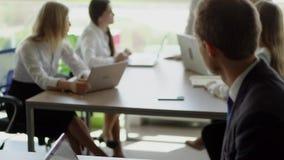 Een zakenman die op zijn laptop typen Chef- verklarend nieuw idee aan arbeiders op de achtergrond stock video