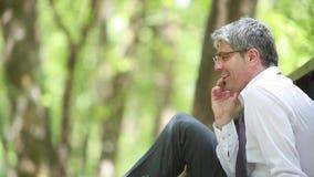 Een zakenman die op zijn mobiele telefoon spreken stock videobeelden