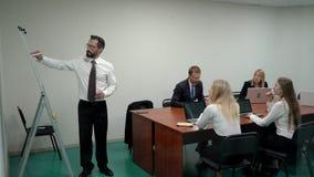 Een zakenman die een tikgrafiek op een witte raad in een vergaderzaal bespreken aan werkend team terwijl status in het bureau stock videobeelden