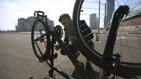 Een zakenman in een kostuum onderzoekt een fiets stock videobeelden