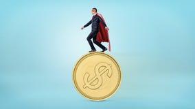 Een zakenman in een rode superherokaap die op de rand van een reuze gouden muntstuk met een USD-teken in evenwicht brengen Royalty-vrije Stock Foto