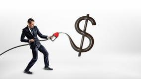 Een zakenman houdt een benzinepomppijp en maakt een reusachtig zwart glanzend USD-teken op een witte achtergrond Royalty-vrije Stock Foto's
