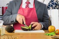 Een zakenman in kostuum en rode band die schort scherpe avocado in de helft met een mes op een houten scherpe raad in de keuken d stock foto's