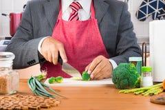 Een zakenman in kostuum en rode band die rode schort en scherpe broccoli dragen en groenten met een binnen mes op een houten sche royalty-vrije stock afbeeldingen