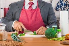 Een zakenman in kostuum en rode band die rode schort en scherpe broccoli dragen en groenten met een binnen mes op een houten sche royalty-vrije stock foto's