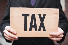 Een zakenman in een kostuum houdt een kartontablet met de inschrijvings 'belasting stock foto
