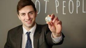 Een zakenman in een kostuum houdt in zijn hand een zilveren bitcoin stock video