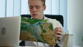 Een zakenman met bekijkt een kaart in het bureau stock video