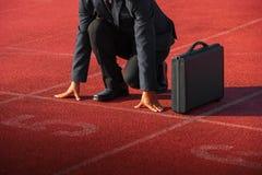 Een zakenman op een spoor klaar voor ras in zaken stock foto