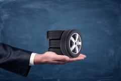 Een zakenman` s hand op blauwe bordachtergrond die vier uiterst kleine autowielen houden stock afbeeldingen