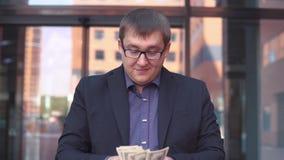 Een zakenman telt geld die zich dichtbij het commerciële centrum bevinden die een goede stemming hebben HD Langzame Motie stock video