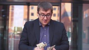 Een zakenman telt geld die zich dichtbij het commerciële centrum bevinden HD stock video
