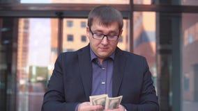 Een zakenman telt geld die zich dichtbij het commerciële centrum bevinden HD Langzame Motie stock video