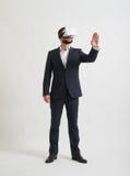 Een zakenman in virtuele werkelijkheidsglazen die somethi in de juiste stand brengen te raken Stock Afbeelding