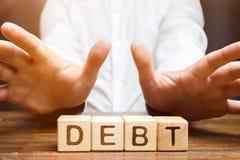 Een zakenman is weg geschermd van schuld Weigering van leningen met hoge rentevoeten, dure leningen Onvermogen om de schuld te be stock afbeeldingen