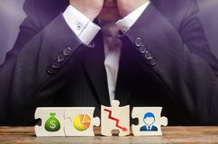 Een zakenman zit in wanhoop en behandelt zijn gezicht met zijn handen Verkeerd bedrijfsmodel, unprofitability en ondoelmatigheid  stock foto