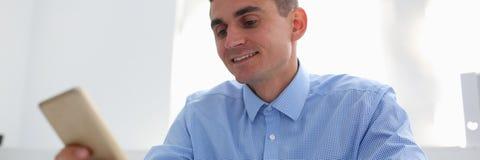Een zakenmanmakelaar in onroerend goed houdt smartphone in hand stock afbeeldingen