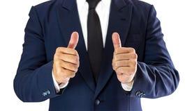 Een zakenmantribunes elegant gekleed in een blauwe kostuum en een duim royalty-vrije stock foto's