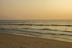 Een zandig strand met vele voetafdrukken op de achtergrond van de golven van de oceaan en grijze roze hemel van zonsondergang royalty-vrije stock foto
