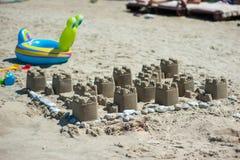 Een zandkasteel op een zandig die strand, tegen een heldere blauwe de zomerhemel wordt geplaatst stock foto's