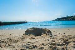Een zandkasteel op een zandig die strand, tegen een heldere blauwe de zomerhemel wordt geplaatst stock foto