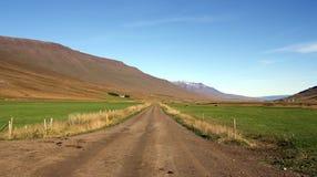 Een zandweg tussen landbouwbedrijven en heuvels in IJsland stock afbeelding
