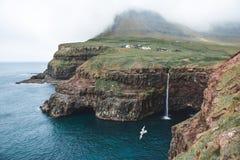 Een zeemeeuw vliegt door Mulafossur Waterfall royalty-vrije stock fotografie