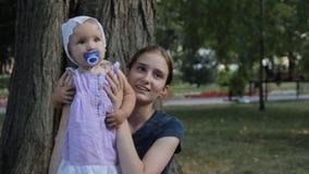 Een zeer jong kindermeisje die een babymeisje met een soother in haar overlapping hebben stock video